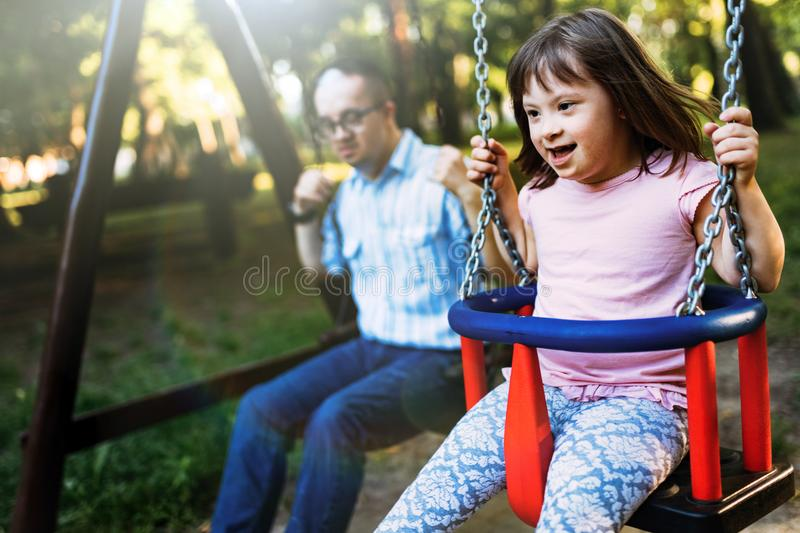 Portrait of man and girl with down syndrome swinging stock photography