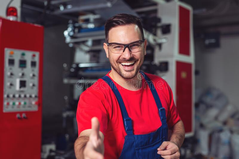 Portrait of a man giving an handshake in an industrial facility. Portrait of a young man giving an handshake in an industrial facility royalty free stock photography