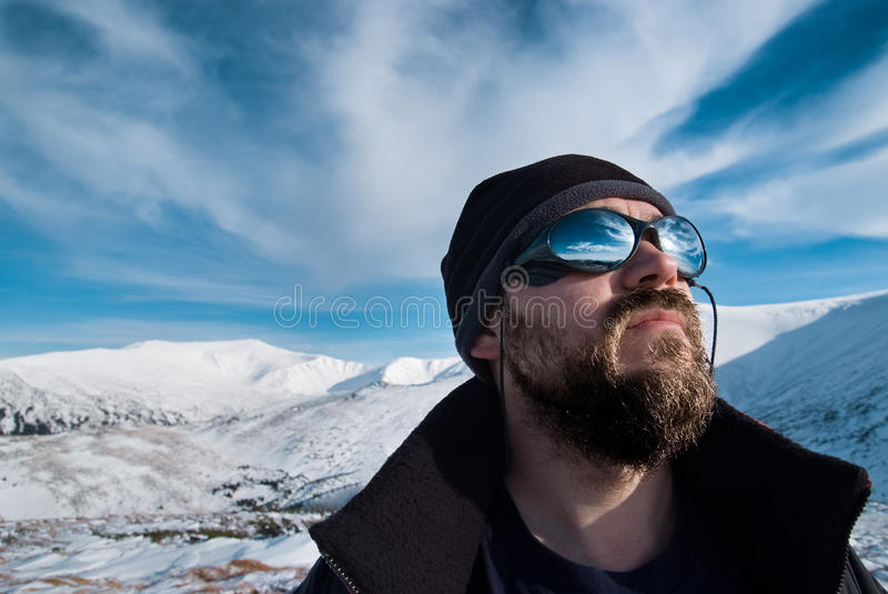 Portrait of a man with glasses and a beard in the snowy mountains stock photography