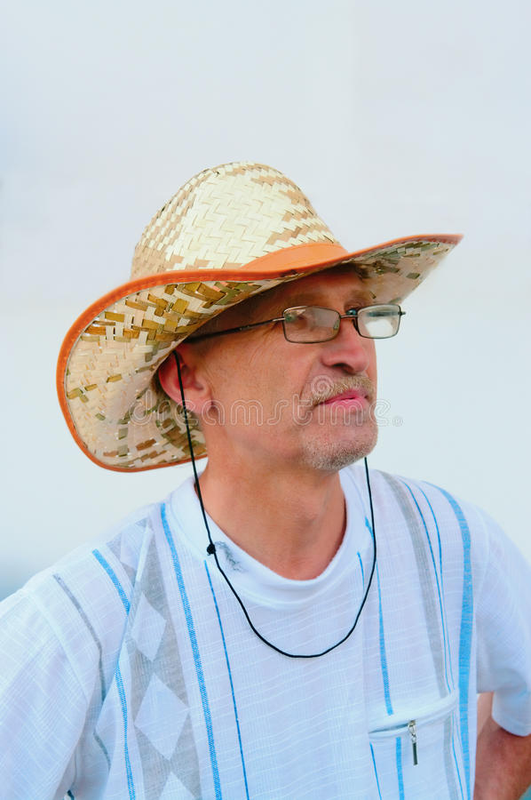Portrait of the man in glasses and a straw hat stock photo