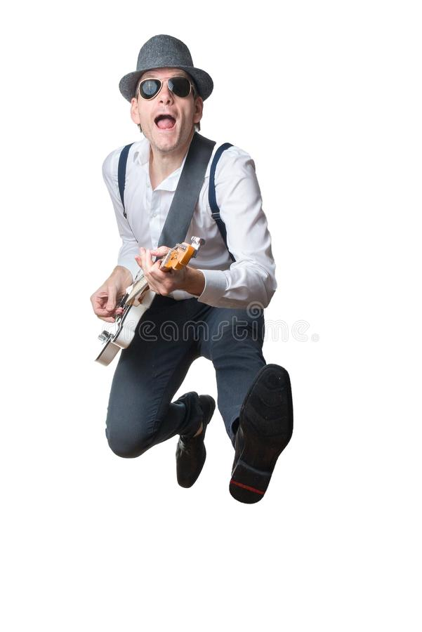 Man with hat plays electric guitar and jumps in the air royalty free stock photos