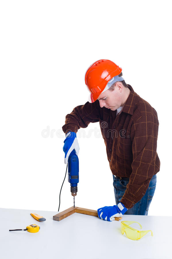 Portrait of man in helmet drilling a plank of wood royalty free stock image