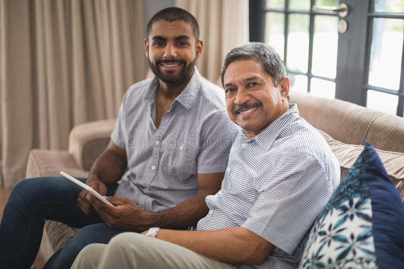 Portrait of man with his father sitting on couch at home royalty free stock image