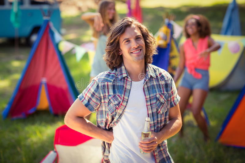 Portrait of man holding beer bottle at campsite. On a sunny day stock image