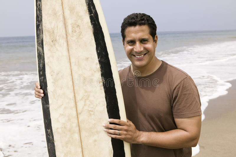 Portrait of man holding surfboard on beach royalty free stock photo