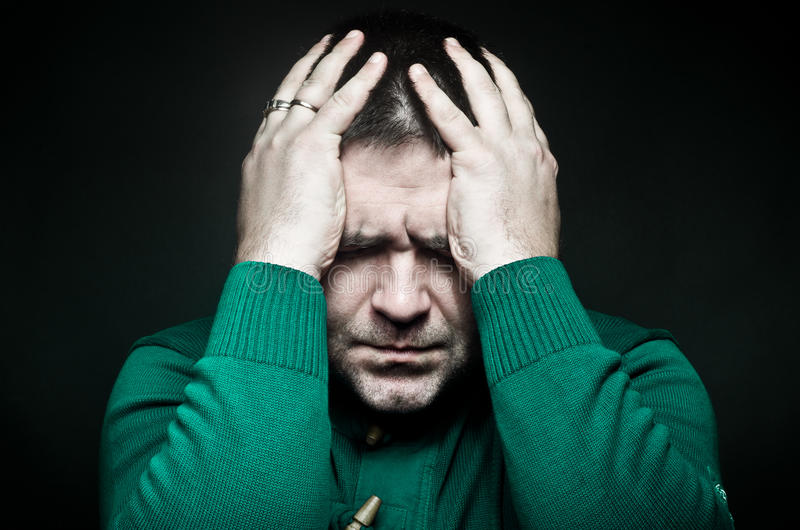 Portrait of a man holding on to head royalty free stock image