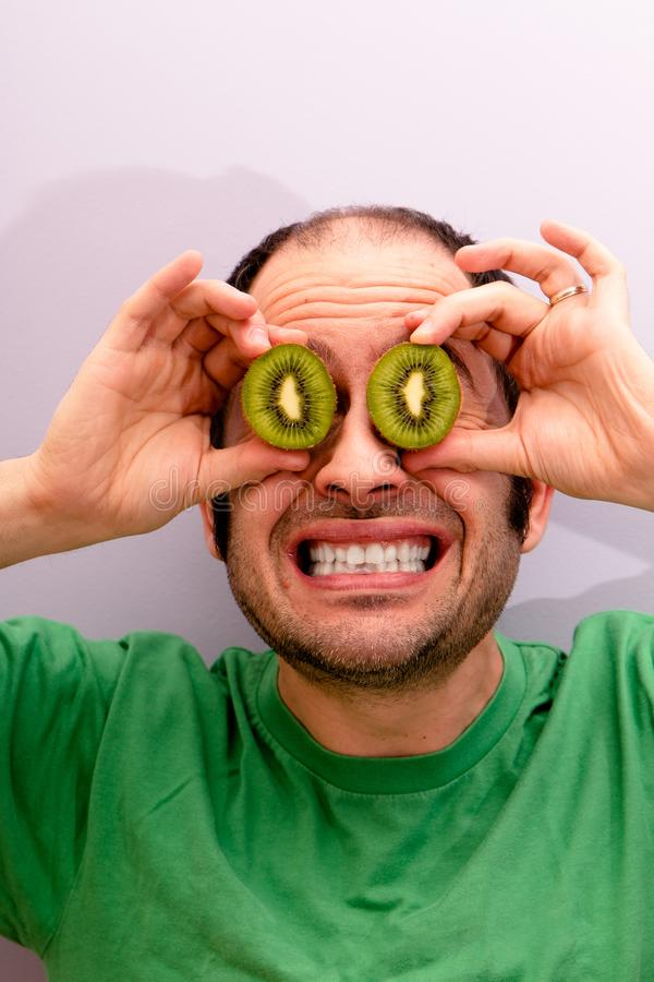 Portrait of a man holding two sliced kiwis in his eyes royalty free stock photos