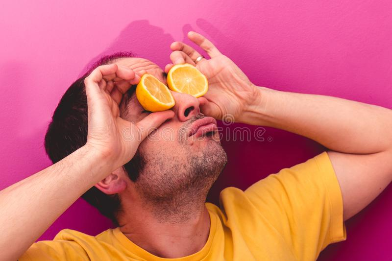 Portrait of a man holding two sliced lemons in his eyes stock photo