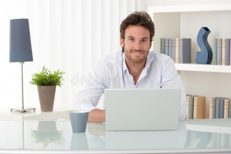 Portrait of man at home with computer. Portrait of goodlooking man sitting at table at home with laptop computer, smiling at camera