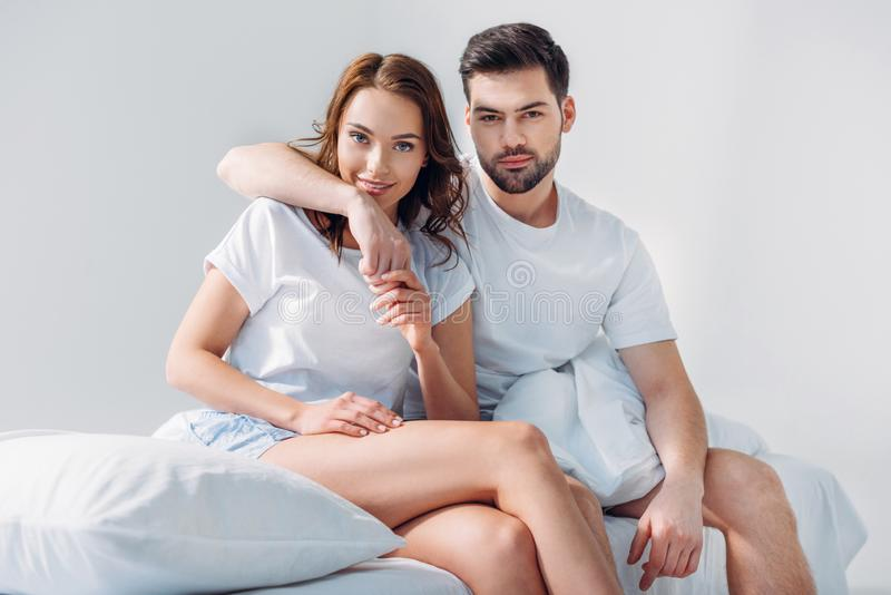 Portrait of man hugging girlfriend while sitting on bed together. Isolated on grey royalty free stock images
