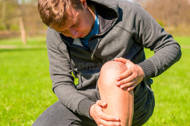 Portrait of man inspecting his injured leg stock photo