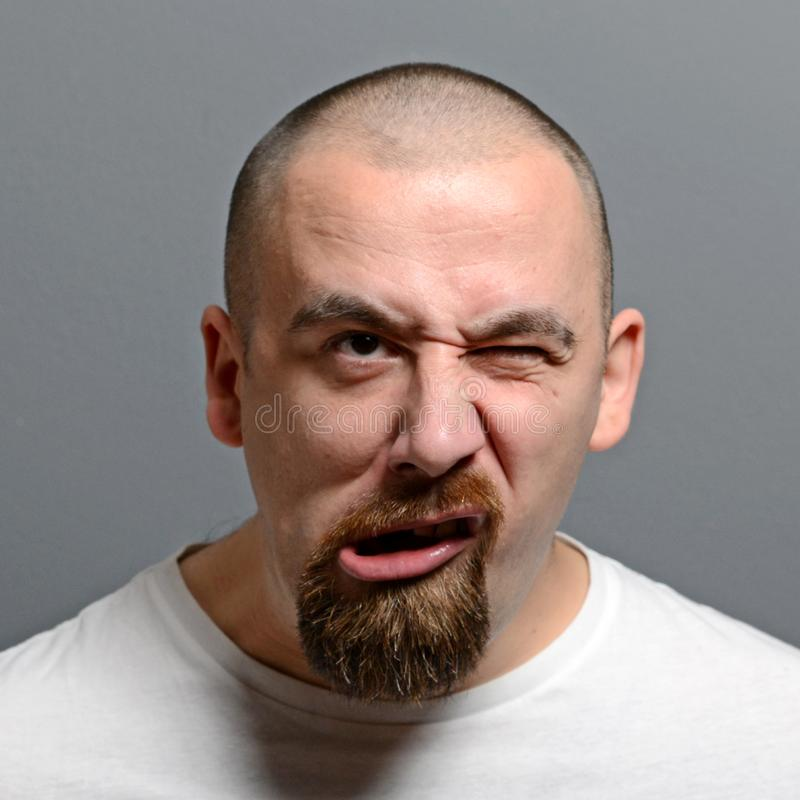 Portrait of a man making funny face against gray background royalty free stock image