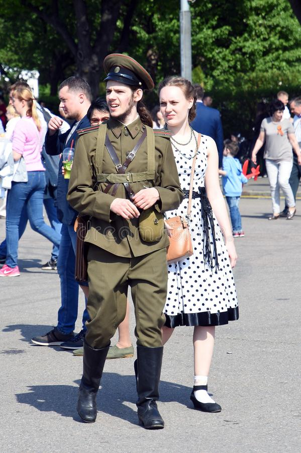 Portrait of a man in military uniform and a woman in historic dress. Victory day celebrations in Moscow, May 09, 2019, Gorky park. It is a tradition - to give royalty free stock photos