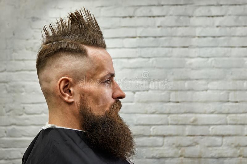 Portrait of a man with a mohawk and beard in a barber chair against a brick wall. close up, brick background, copy space royalty free stock images