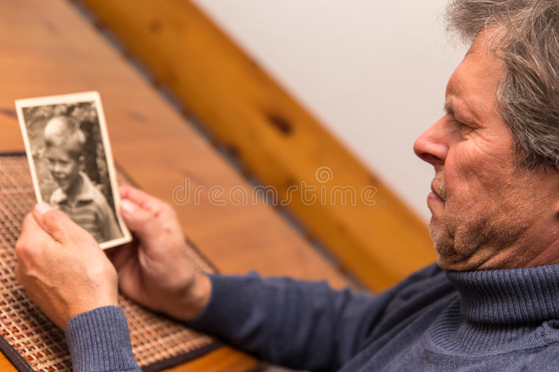 Portrait of a man with old photo. Senior adult watching a photo from his childhood royalty free stock photos