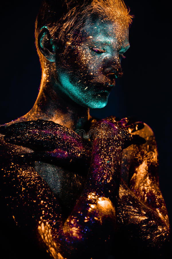 Portrait of a man painted in fluorescent UV colors. Conceptual shot of light and shine fluorescent colors young man`s face royalty free stock images