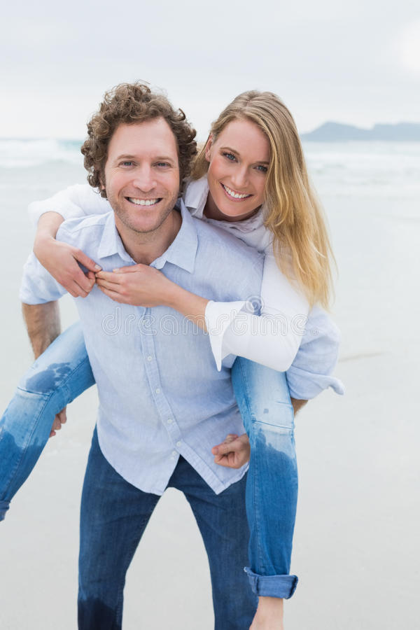 Portrait Of A Man Piggybacking Woman At Beach Stock Images