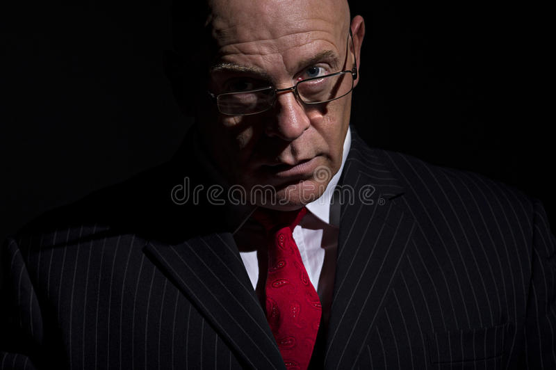 Portrait of man in pin stripe suit. Low key portrait of a mature male in a dark pinstripe suit. He has a serious expression on his face. He has glasses and can stock photography