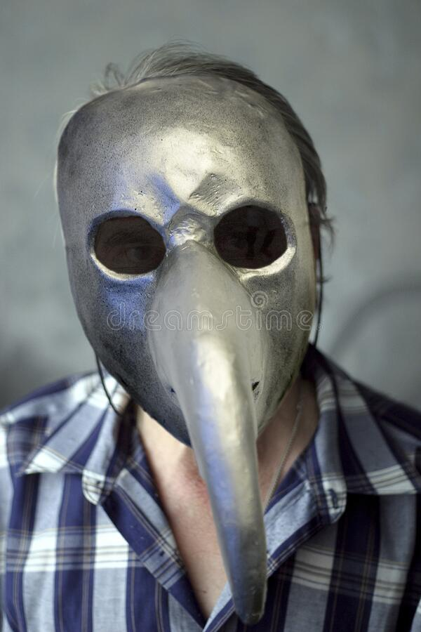 Man in a plague mask. Portrait of a man in a plague mask in a working environment stock photography