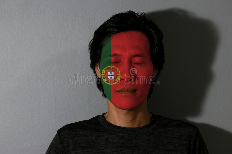 Portrait of a man with Portugal flag painted on his face and close eyes with black shadow on grey background. stock photography