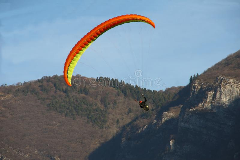 Image of man practicing parachuting over mountain landscape stock image