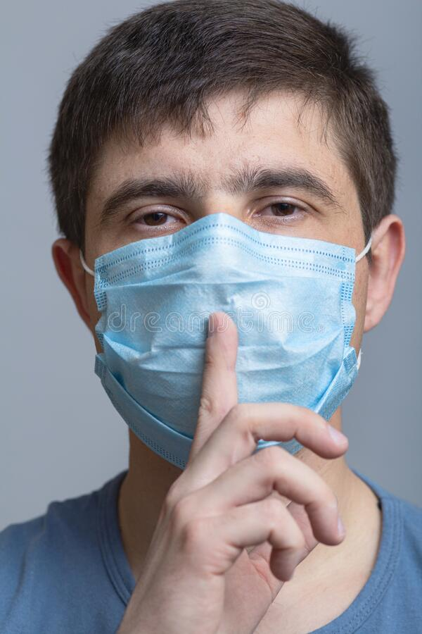 Portrait of a man in a protective medical mask on face showing sign of silence gesture putting finger in mouth and lips, concept. Medical secrecy, moment of royalty free stock photos