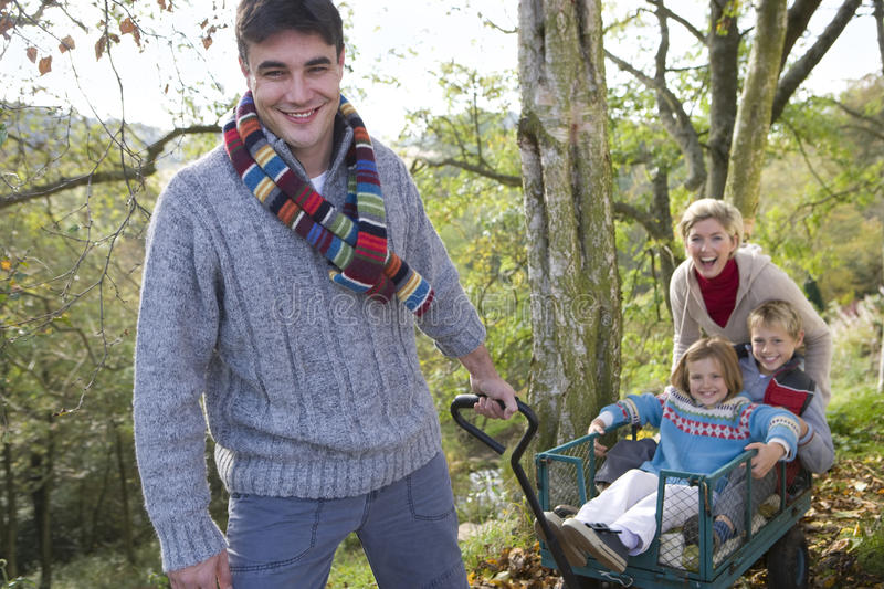 Portrait of a man pulling his children in a wheelbarrow, with his wife in the background royalty free stock image
