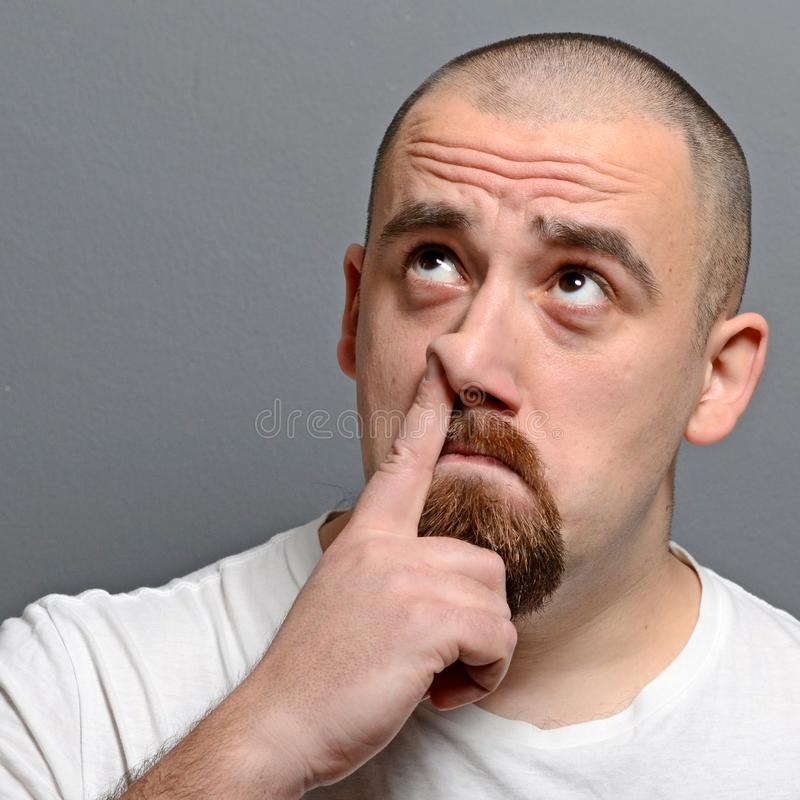 Portrait of a man putting finger in his nose against gray background royalty free stock image