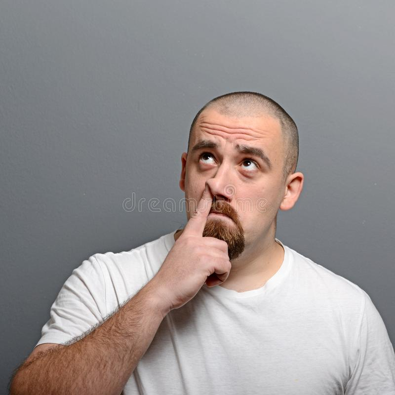 Portrait of a man putting finger in his nose against gray background stock image
