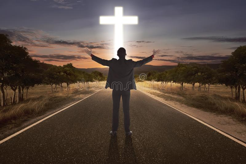 Portrait of man raising hand while praying to god with bright cr. Oss at the end of the road royalty free stock images