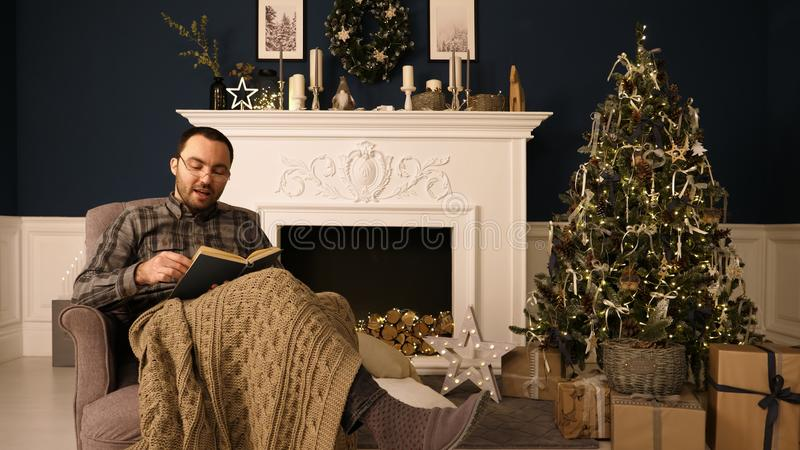 Portrait of a man reading book to the camera on Christmas evening. stock image