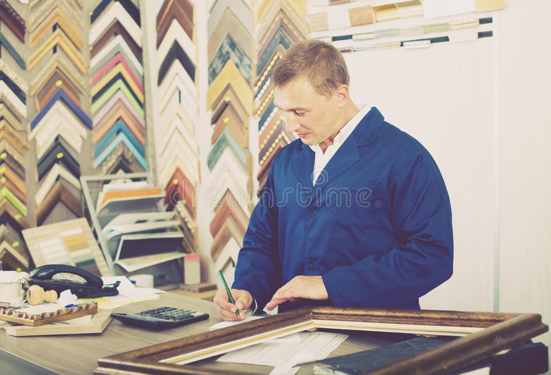 Portrait of man seller working with picture frames in atelier. Portrait of glad american man seller working with picture frames in atelier royalty free stock images