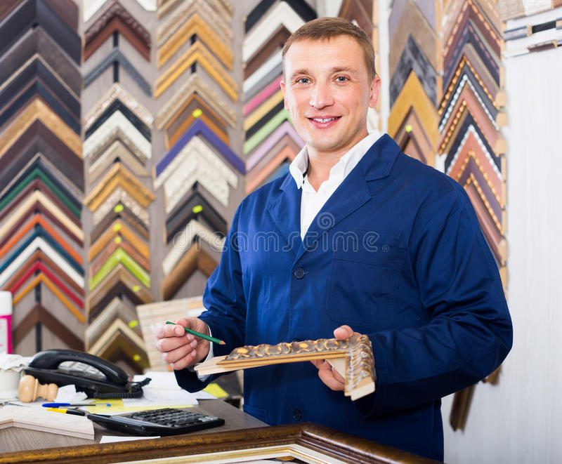 Portrait of man seller working with picture frames in atelier. Portrait of glad european man seller working with picture frames in atelier stock image