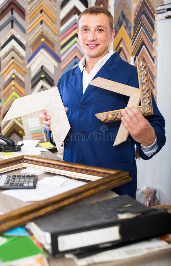 Portrait of man seller working with picture frames in atelier. Portrait of happy man seller working with picture frames in atelier stock photos