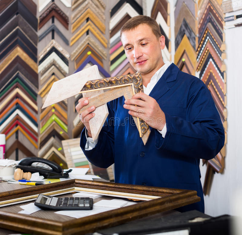 Portrait of man seller working with picture frames in atelier. Portrait of happy european man seller working with picture frames in atelier royalty free stock images