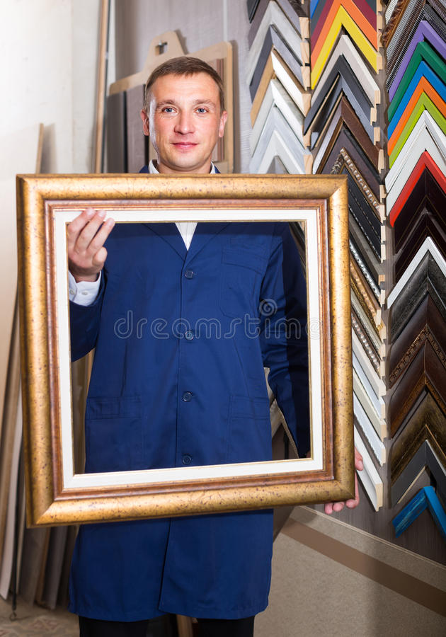 Portrait of man seller working with picture frames in atelier. Portrait of smiling spanish man seller working with picture frames in atelier royalty free stock image