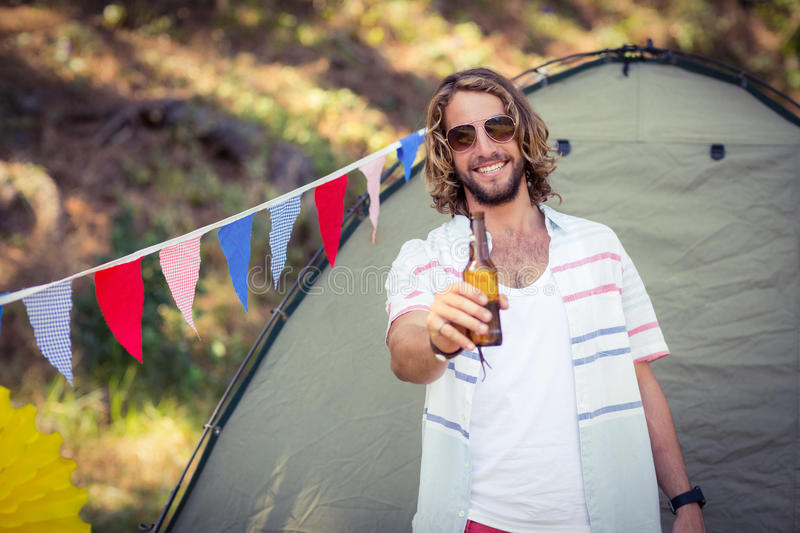 Portrait of man showing beer bottle at campsite. On a sunny day royalty free stock image