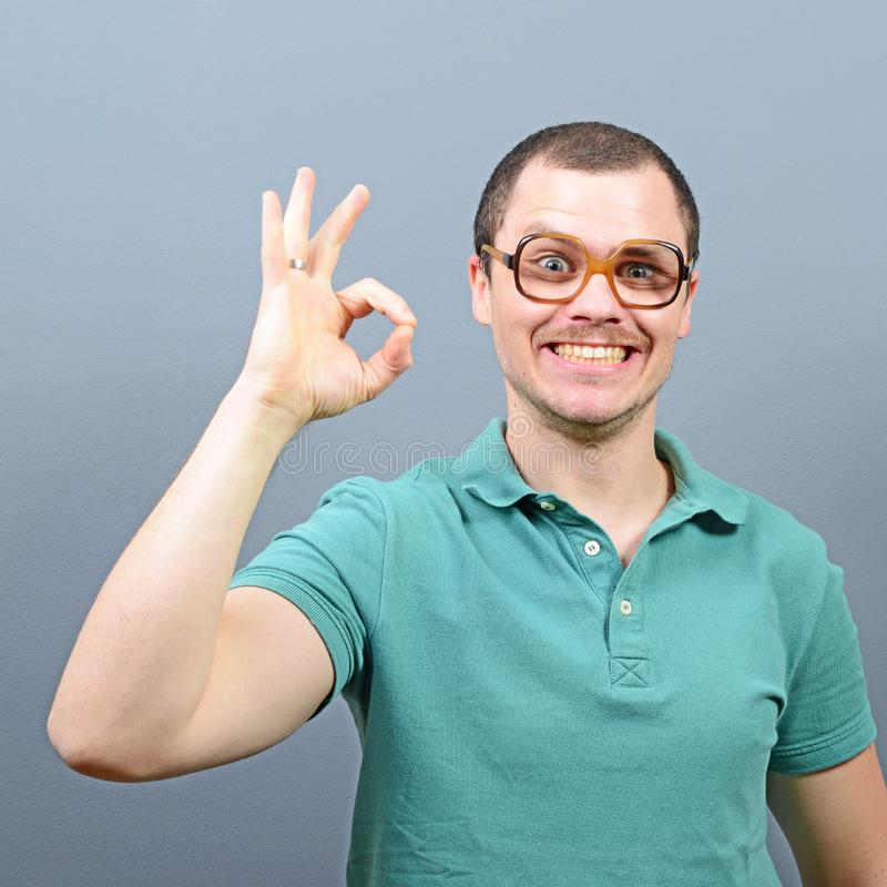 Portrait of a man showing ok sign against gray background stock photography