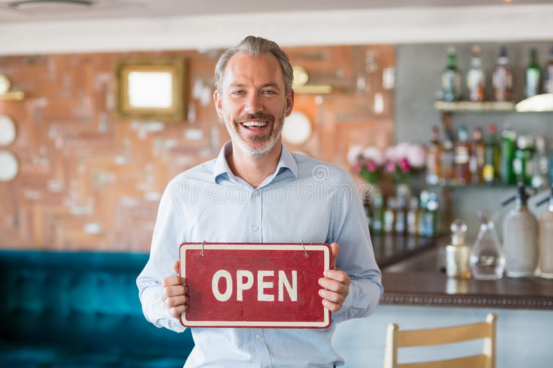 Portrait of man showing signboard with open sign. In restaurant royalty free stock photography