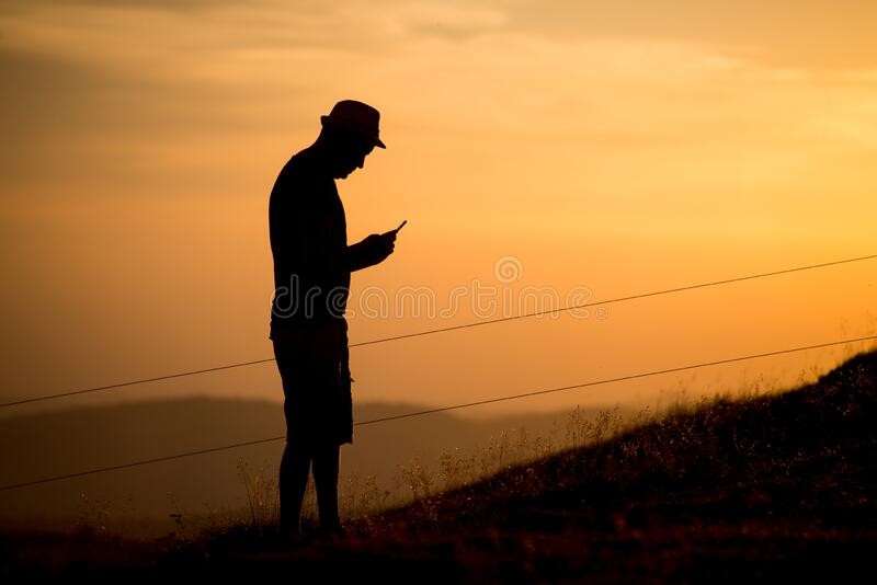 Man silhouette standing at the top of the mountain looking his smartpnone in hands on sunset background stock photography