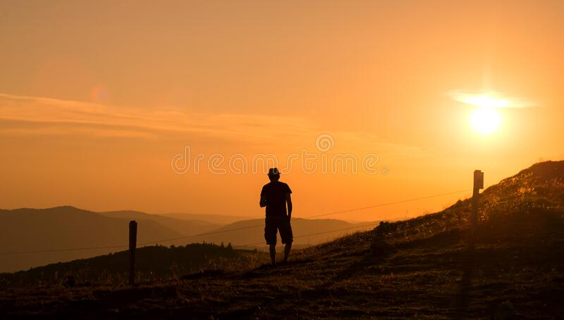 Man silhouette standing at the top of the mountain looking the landscape on sunset background royalty free stock images