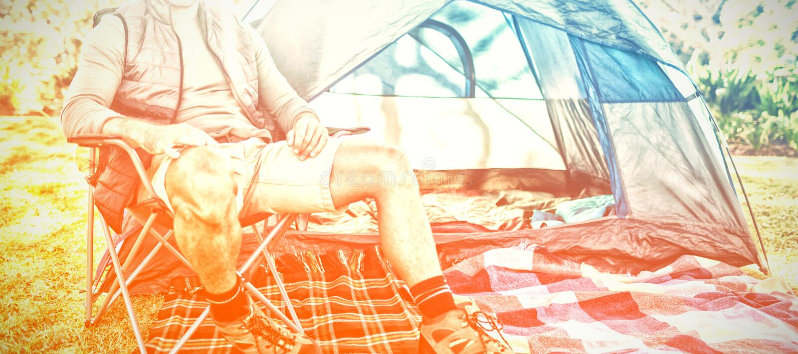 Man sitting on the chair outside the tent stock photography
