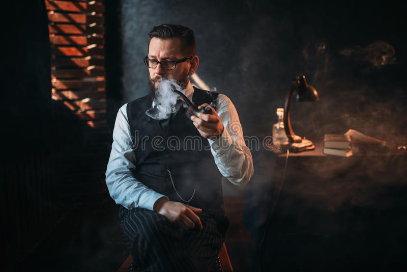 Portrait of man sitting on chair and smoking pipe stock image