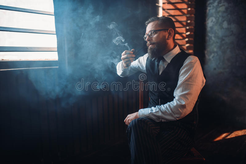 Portrait of man sitting on chair and smoking pipe. Portrait of bearded man in glasses sitting on a chair and smoking pipe. Writer, journalist, literature author stock photo