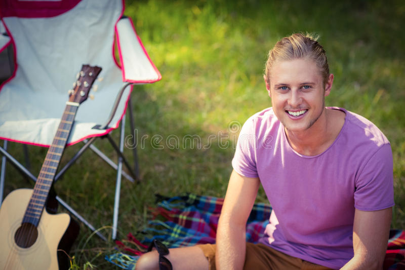 Portrait of man sitting on grass at campsite. On a sunny day stock images