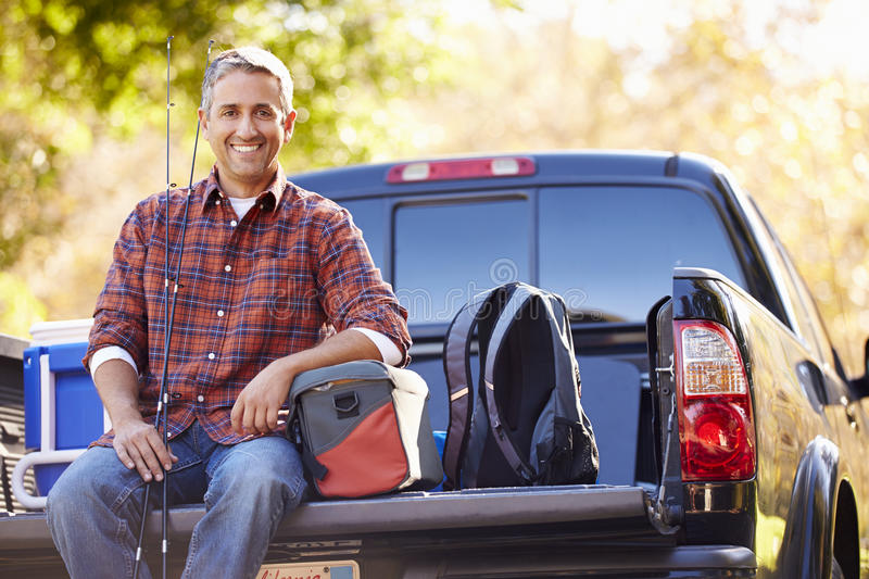 Portrait Of Man Sitting In Pick Up Truck On Camping Holiday. Smiling At Camera stock photography
