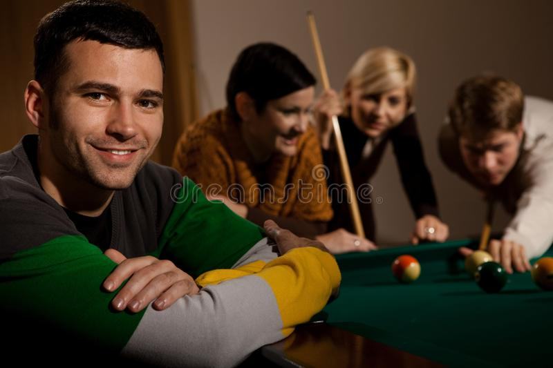 Portrait of man at snooker table. Portrait of smiling young men at snooker table, friends playing in background royalty free stock images