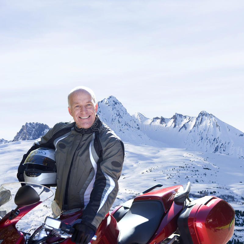 Portrait of man and snowmobile with snow covered mountains in background royalty free stock photo
