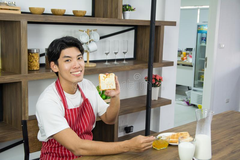 Portrait of man spread bread jam in red apron with a glass of milk stock photo