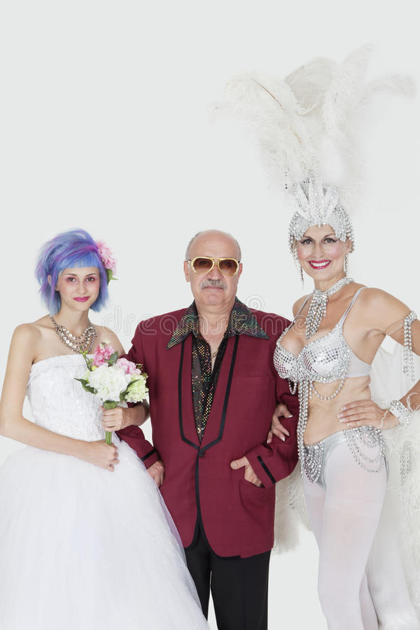 Download Portrait Of Man Standing Arms In Arms With Senior Showgirl And Daughter In Wedding Dress Over Gray Background Stock Photo - Image: 30851856